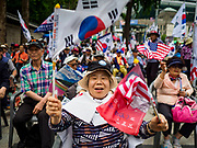 09 JUNE 2018 - SEOUL, SOUTH KOREA: A woman cheers during a pro-American rally in downtown Seoul. Participants said they wanted to thank the US for supporting South Korea and they hope the US will continue to support South Korea. Many were also opposed to ongoing negotiations with North Korea because they don't think Kim Jong-un can be trusted to denuclearize or to not attack South Korea.     PHOTO BY JACK KURTZ