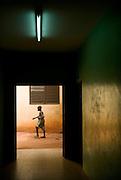 A boy walking outside a house in Benin on February 23, 2008.