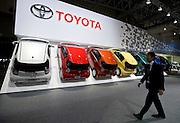 A staffer walks past a row of Toyota Motor Corp.'s iQ compact cars that are displayed during a pre-opening day for the media two days before the start of the 41st Tokyo Motor Show 2009 at Makuhari Messe in Chiba, Japan on Wed., Oct. 21 2009..Photographer: Robert Gilhooly