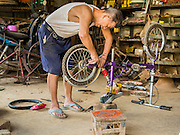 26 APRIL 2014 - TACHILEIK, SHAN STATE, MYANMAR: A man repairs bicycles in his shop in Tachileik, Shan State, Myanmar.      PHOTO BY JACK KURTZ