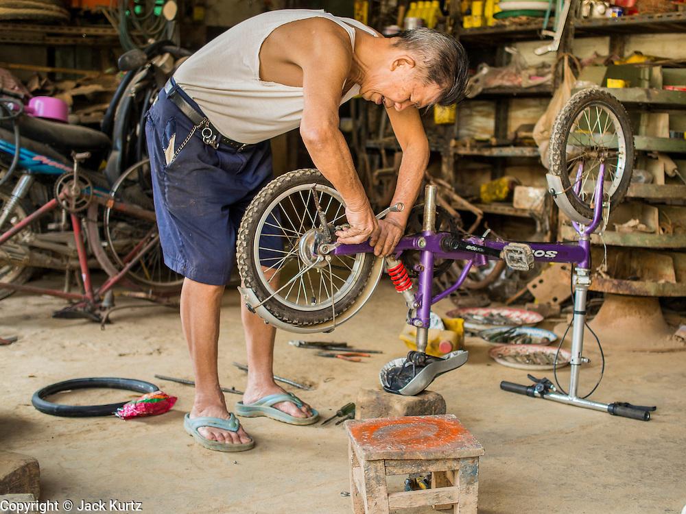 26 APRIL 2014 - TACHILEIK, SHAN STATE, MYANMAR: A man repairs bicycles in his shop in Tachileik, Shan State, Myanmar.      PHOTO BY JACK KURTZ