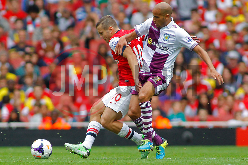Arsenal's Jack Wilshere and Aston Villa's Karim El Ahmadi compete for the ball  - Photo mandatory by-line: Mitch Gunn/JMP - Tel: Mobile: 07966 386802 17/08/2013 - SPORT - FOOTBALL - Emirates Stadium - London -  Arsenal V Aston Villa - Barclays Premier League