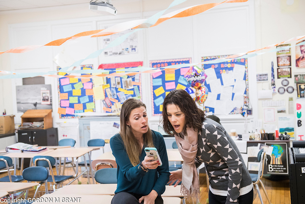 Cara Nelson, left, a seventh grade social studies teacher at East Hampton Middle School, shows a photo of a fellow competitors foot blister to teacher Adrienne Posillico, upon returning from her recent trip that involved running seven marathons in seven days on seven continents, in East Hampton, Feb. 7, 2018. This was Nelson's first day back to school after finishing her last marathon on Monday in Miami.