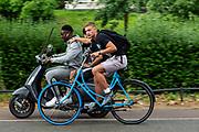 In Utrecht hangt een fietsende jongen aan een scooter.<br /> <br /> In Utrecht a boy on a bicycles holds on to a scooter.