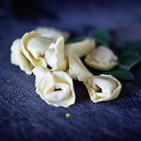 Bunch of raw tortellini pasta with sage on a dark background. Shallow depth of field.