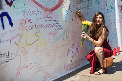 © Licensed to London News Pictures. 20/06/2017. London, UK. A woman writes a message of support outside Finsbury Park Mosque in North London, close to the scene of the attack. A man drove a white van into a crowd of Muslims in Finsbury Park after Ramadan prayers early on the morning of Monday 19 June 2017, killing one man and injuring a number of others. Photo credit: Rob Pinney/LNP