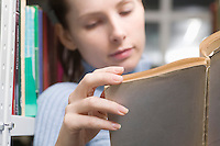 Young woman reads book in library