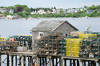 A fishing shack on Beals Island, Maine is walled in by piles of lobster traps. The town of Jonesport is visible across the bay.
