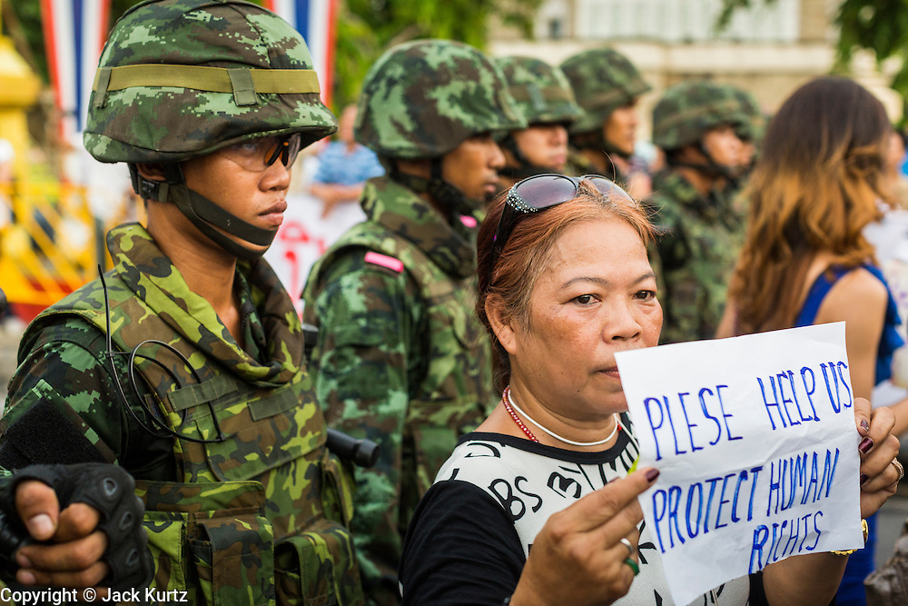 26 MAY 2014 - BANGKOK, THAILAND:   A woman stands in front of riot police protesting against the coup in Thailand at Victory Monument during a pro-democracy rally in Bangkok. About two thousand people protested against the coup in Bangkok. It was the third straight day of large pro-democracy rallies in the Thai capital as the army continued to tighten its grip on Thai life.   PHOTO BY JACK KURTZ