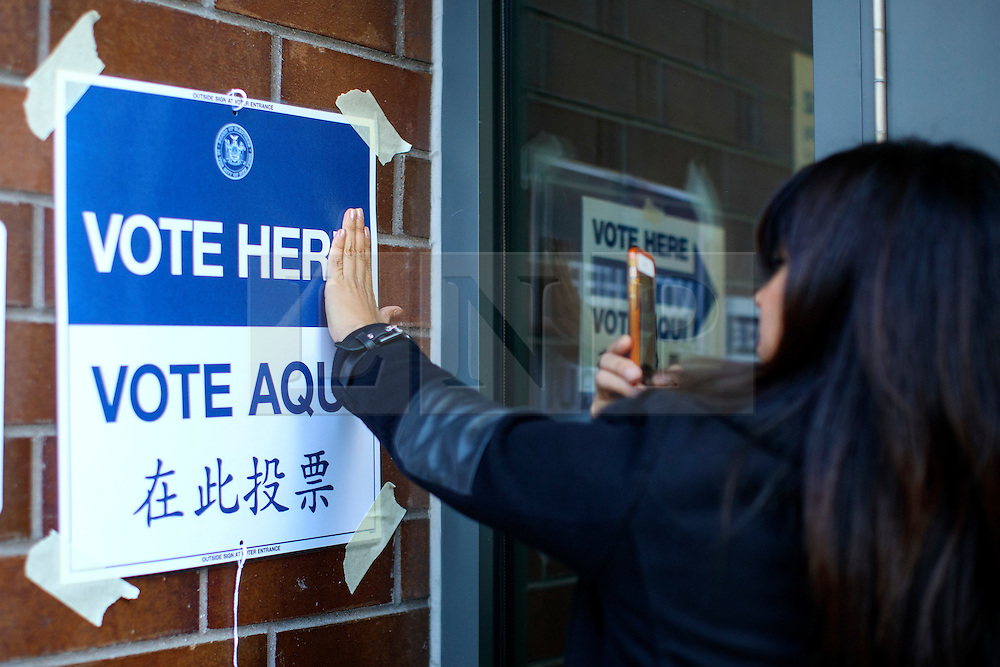 © Licensed to London News Pictures. 08/11/2016. New York CIty, USA. A voter takes a picture with a polling station sign to read 'Vote her' outside a polling station in Manhattan, New York City on Tuesday, 8 November, the day of the presidential election in the United States of America. Photo credit: Tolga Akmen/LNP