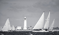 Yachts pass Hurst light while competing in the JPMorgan Asset Management Round the Island Race. Isle of Wight.<br /> Picture date: Saturday June 27, 2015.<br /> Photograph by Christopher Ison &copy;<br /> 07544044177<br /> chris@christopherison.com<br /> www.christopherison.com