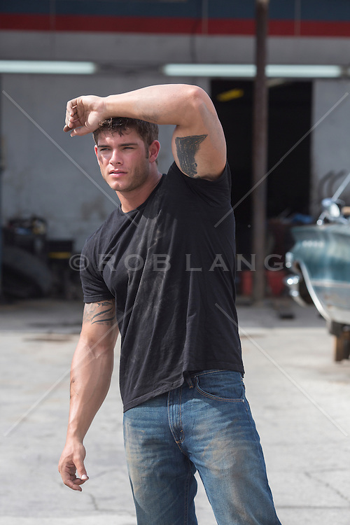 sexy man with tattoos standing outdoor by a car repair shop