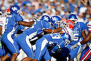 Kentucky football players make a tackle against Florida at Commonwealth Stadium. (Photo by Joe Robbins)