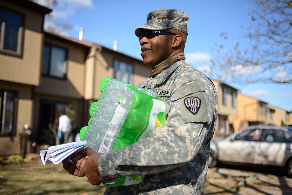 Army National Guard Specialist Wayne Matthews holds water and inspects Midland Beach of Staten Island during hurricane Sandy relief clean up.