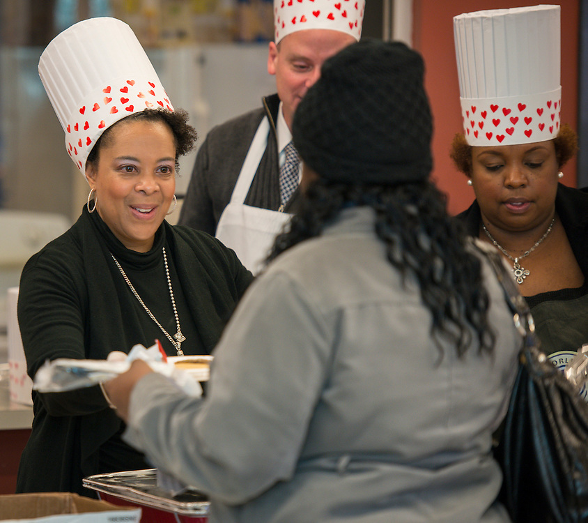 """Transportation managers Chandra Robertson, left, Nathan Graf, center, and Tesha Foster, right, serve breakfast to bus drivers coming in from their morning routes at the Northwest bus yard as part of the """"Love the Bus"""" month celebration, February 13, 2014."""