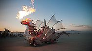 A dragon art car breaths fire on the playa at Burning Man