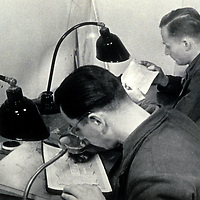German technicians retouch master renderings of counterfeit British pound notes during World War II in Operation Bernhard. This work was conducted during the Operation Andreas phase of the countering scheme with offices in Berlin.