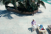 An elderly couple relaxing in chairs in the pool area of a Miami Beach, Florida hotel