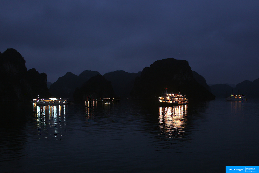 Tourist Junks moored at night time in Ha Long Bay, Vietnam. The bay consists of a dense cluster of 1,969 limestone monolithic islands. Ha Long Bay, is a UNESCO World Heritage Site, and a popular tourist destination. Ha Long, Bay, Vietnam. 11th March 2012. Photo Tim Clayton