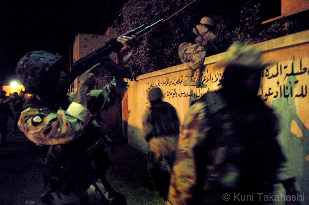 Iraqi special forces, called Shahwanis, enter the grounds of a house during an early morning raid in Musayyab.