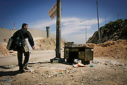 A man carries computers on a desolate pathway bordering Jerusalem and the West Bank.