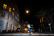 A member of the Adidas Runners Copenhagen team dashes across a well-lit street in the centre of the Danish capital
