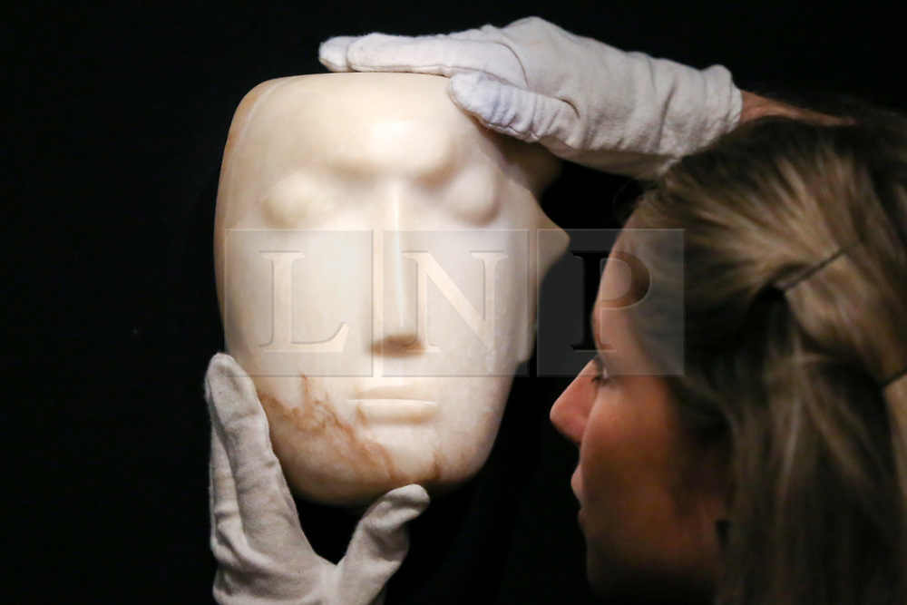 "© Licensed to London News Pictures. 12/11/2018. London, UK. A staff member holds ""The Man Behind the Mask"", a Henry Moore's masterpiece (British, 1898-1986). (Estimate: £1,000,000-1,500,000). The work is one of 12 known, small carvings by Moore titled Mask, and, uniquely, is the only one carved from alabaster.<br /> Bonhams Modern British and Irish Art photocall. Auction to be held on 14 November 2018. Photo credit: Dinendra Haria/LNP"