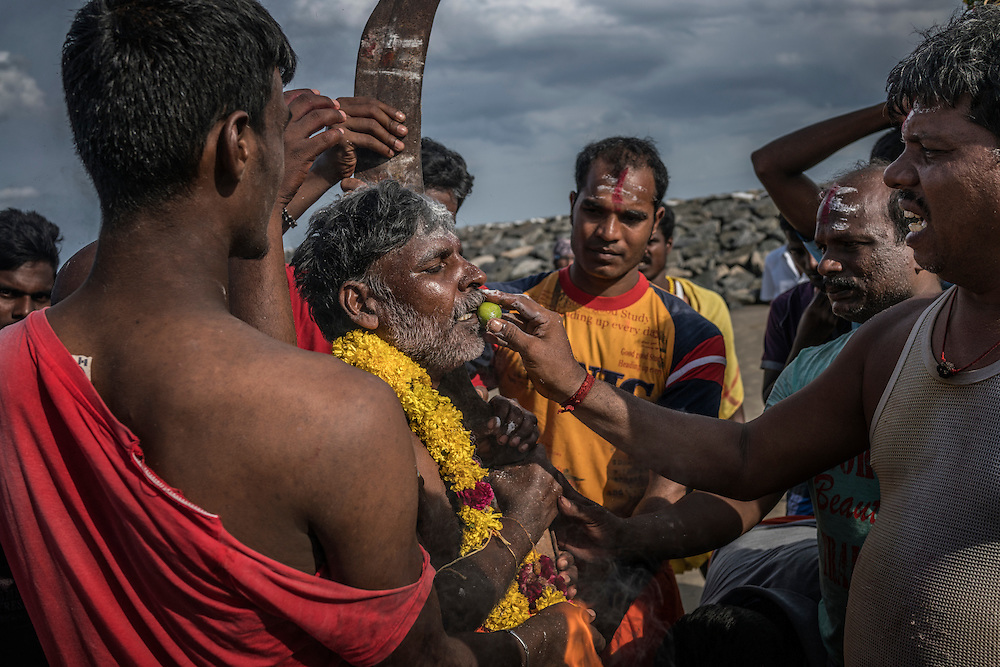 A village man, deep a trance, is about to be fed a citrus fruit on the the beach as part of the Ganesh Chaturthi Festival.  Tiruchchepuram, Tamil Nadu, India.