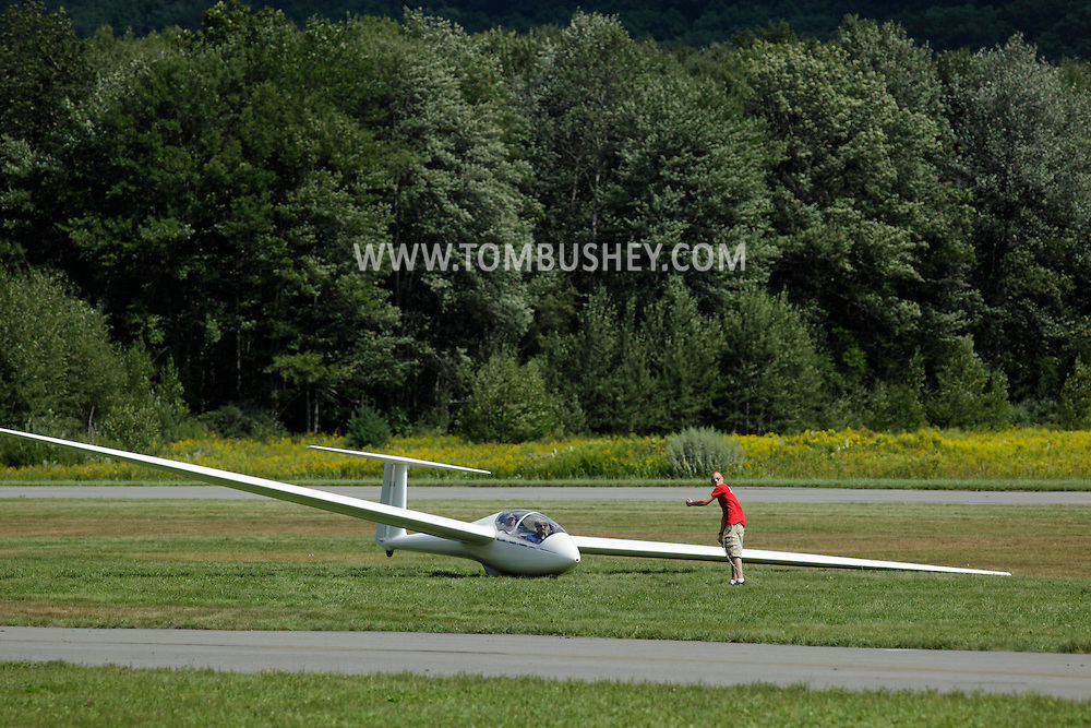 Wurtsboro, NY - An airport worker prepares to attatch the tow rope to a glider at Wurtsboro Airport on Aug. 30, 2009.