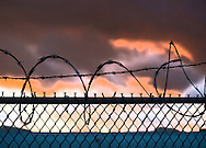 Sunset in Long Island. Barbed wire tops chain link fence separating properties. Black barb razor wire atop chain link fence during sunset, USA