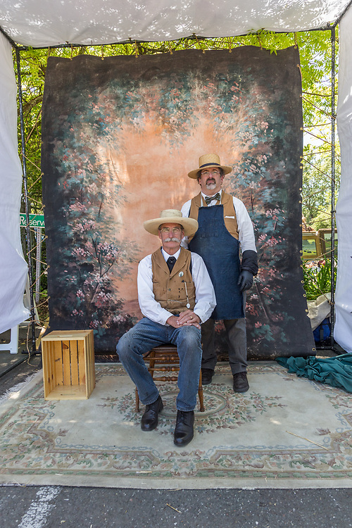 "Photographer Bruce Morton with his assistant, Alan, pose inside their portable ""tintype"" portrait studio at the Petaluma Antique Fair."
