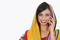 Portrait of beautiful Indian woman in traditional wear answering phone call over gray background