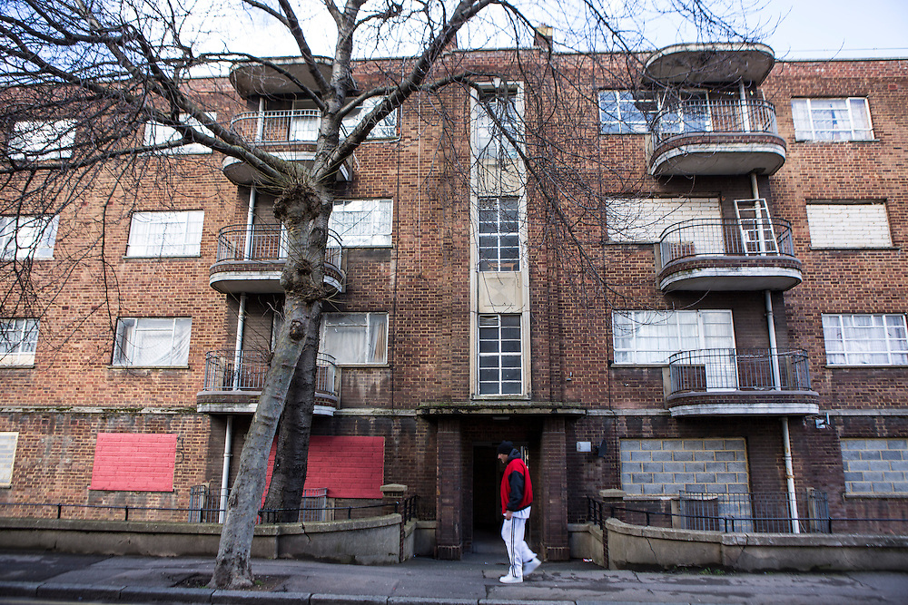 A British man walks past a block of social housing flats which are derelict and have been mostly boarded up to prevent entry and squatting on Whiston Road, Hackney, London. There are thousands of derelict and abandoned homes in London at the same time an affordable housing crisis with many people homeless or living in inadequate situation.
