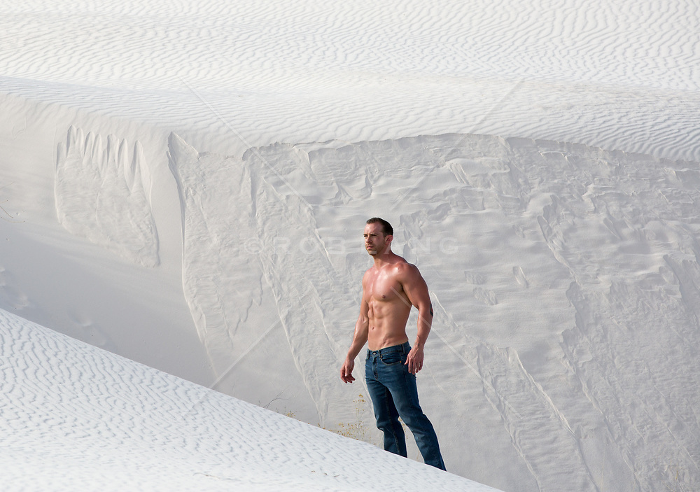 hot shirtless man in jeans on a sand dune