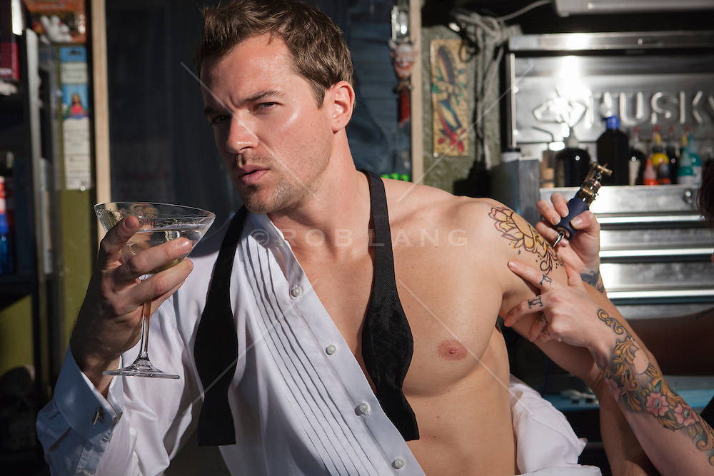 Sexy man in an open tuxedo shirt holding a martini while getting a tattoo