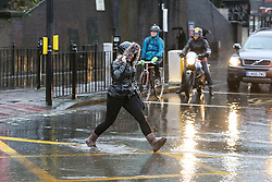 © Licensed to London News Pictures. 20/12/12/019. London, UK. A woman is seen walking through a flood on Green Lanes, Harringay in North London, caused by overnight heavy rainfall and a pipe burst.  Photo credit: Dinendra Haria/LNP