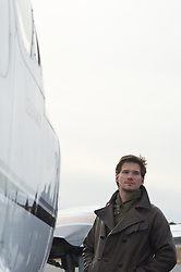 Man In leather jacket standing  outside an airplane