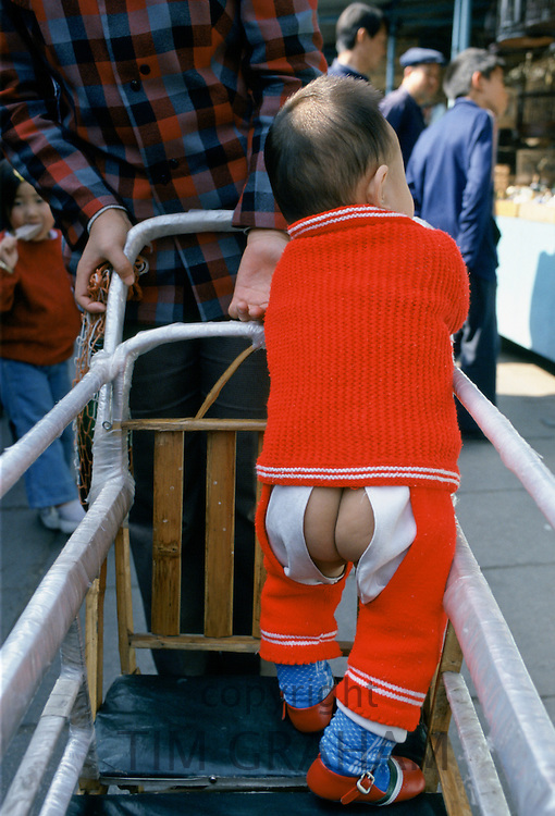Chinese child with traditional open trousers in place of nappy, China in the 1980s