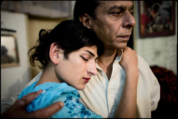 """Kastouri (left side),  a young transvestite of 16 years, hugs his Papa gay K. (on the right), 42 years old. Transvestites people have created a community, a kind of an hierarchical staircase, based on rules handed down by generations.  Evening in Lahore, Pakistan on Monday, December 01 2008.....""""Not men nor women"""". Just Hijira, Kusra. Painted lips, Kajal surrounding their eyes and colourful veils..Pakistan is today considered a strongly, foundamentalist as well, islamic country. But under its reputation, above all over the talebans' continuos advancing, stirs a completely extraneous world, a multiethnic mixed society. Transvestites make part of it, despite this would not be admitted by a strict law. Third gender, the Hijira are born as men (often ermaphrodites) or with an ambiguous genital situation, and they have their testicles and penis removed through a - often brutal - surgical operation. The peculiarity is that this operation does not contemplate the reconstruction of a female organ. This is the reason why they are not considered as men nor women, just Hijira. They are often discriminated, persecuted  and taxed with being men prostitutes in the muslim areas. The members of this chast perform dances during celebrations, especially during weddings, since it is anciently believed that an EUNUCO's dance and kiss in the wedding day brings good luck to the couple's fertility...To protect the identities of the recorded subjects names and specific .places are fictionals."""