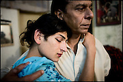 "Kastouri (left side),  a young transvestite of 16 years, hugs his Papa gay K. (on the right), 42 years old. Transvestites people have created a community, a kind of an hierarchical staircase, based on rules handed down by generations.  Evening in Lahore, Pakistan on Monday, December 01 2008.....""Not men nor women"". Just Hijira, Kusra. Painted lips, Kajal surrounding their eyes and colourful veils..Pakistan is today considered a strongly, foundamentalist as well, islamic country. But under its reputation, above all over the talebans' continuos advancing, stirs a completely extraneous world, a multiethnic mixed society. Transvestites make part of it, despite this would not be admitted by a strict law. Third gender, the Hijira are born as men (often ermaphrodites) or with an ambiguous genital situation, and they have their testicles and penis removed through a - often brutal - surgical operation. The peculiarity is that this operation does not contemplate the reconstruction of a female organ. This is the reason why they are not considered as men nor women, just Hijira. They are often discriminated, persecuted  and taxed with being men prostitutes in the muslim areas. The members of this chast perform dances during celebrations, especially during weddings, since it is anciently believed that an EUNUCO's dance and kiss in the wedding day brings good luck to the couple's fertility...To protect the identities of the recorded subjects names and specific .places are fictionals."