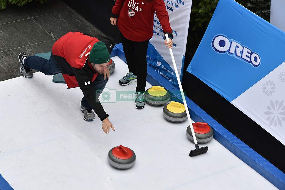 A participant tries his hand at the sport of Curling during the Team USA Winter Fest  - 100 day countdown to the 2018 Winter Olympics, in Times Square, New York, on November 1, 2017. (Photo by Anthony Behar/Sipa USA)