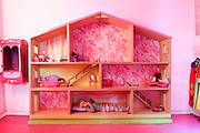 Little girl of four plays inside a giant doll's house in a pink play room