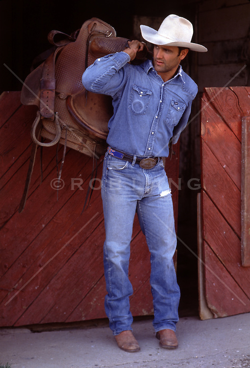 hot cowboy with a saddle by a barn