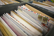Sorted letters are grouped in a drawer at Royal Mail's giant warehouse at the DIRFT logistics park in Daventry, Northamptonshire England. Raised from its neighbours is an Air Mail letter addressed to someone called Rodrigues and with stamps if its unknown country. Each letter faces the same direction for ease of viewing in this enormous complex where some of the UK's 82 million items pass through. Royal Mail handles some 82 million posted items a day. They have a statutory duty to provide a delivery service to 27 million addresses in the UK for letters and for parcels weighing up to 20kg. Six days a week they deliver daily to all addresses in the UK and provides a collection service from 115,000 Post Boxes, 16,000 Post Offices, businesses and organizations throughout the UK and distributed through 72 mail centres and 100 distribution centres.