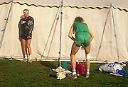 Long-distance London Marathon athletes warm-up and apply vaseline to sensitive areas in Greenwich Park.