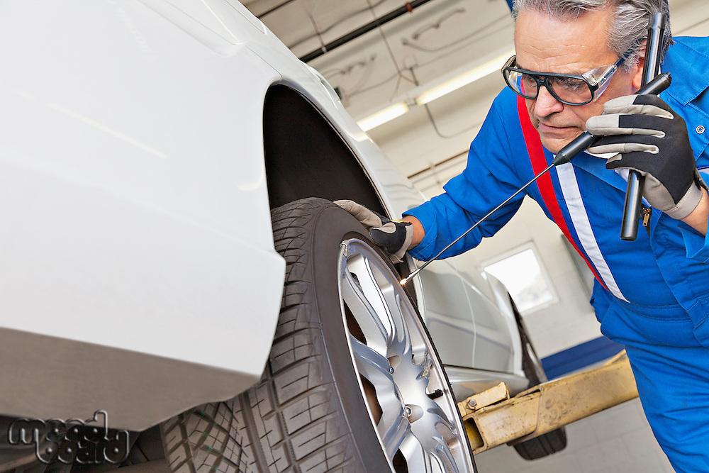 Elderly man working on car tire