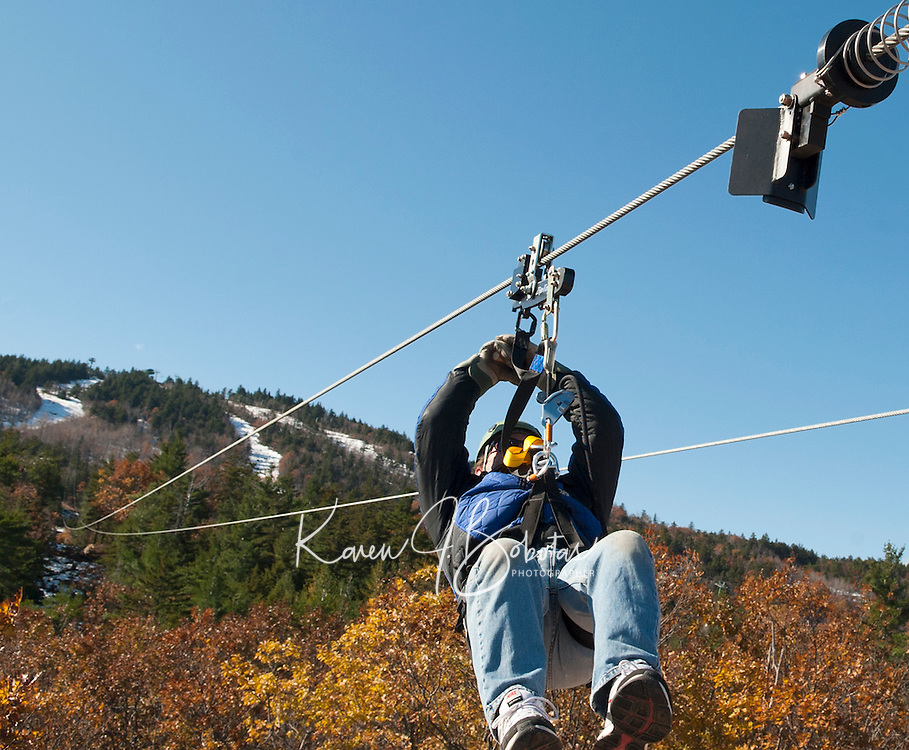 Chuck Lowth takes on the second of three zip lines from the top of Gunstock Mountain Friday morning in prepartion for their opening day of the  ZipTour Mountain Zip Line Adventure Saturday, November 5th.   (Karen Bobotas/for the Laconia Daily Sun)