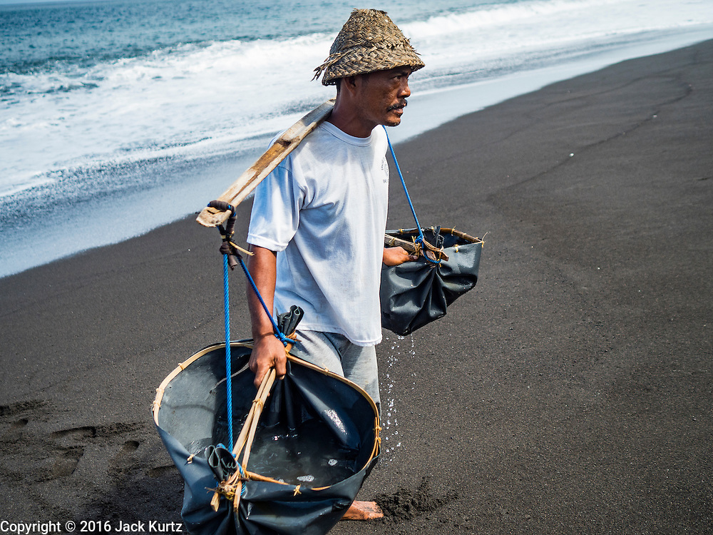 20 JULY 2016  - KUSAMBA, BALI, INDONESIA: A man carries sea water to his salt making area on the beach in Kusamba. Salt makers in Kusamba, on the Bali coast, make salt by sprinkling sea water on a bed of sand and scraping up the salt when the water evaporates. It's a very slow, labor intensive way of making salt.       PHOTO BY JACK KURTZ