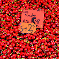 Large Display of Red Sweet Cherries at Viktualienmarkt in Munich, Germany<br /> During June, take a walk through the 240,000 square foot food market called Viktualienmarkt, which is located in the center of Munich, Germany, and you'll quickly find huge displays of sweet cherries among several of the 100 plus stalls. They are red, ripe, smell wonderful and taste even better.  They are produced from over 2 ½ million sweet cherry trees in the country.  Another 1 ½ million trees grow tart cherries, which are mainly reserved for cooking.