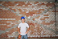 Young construction worker standing by brick wall